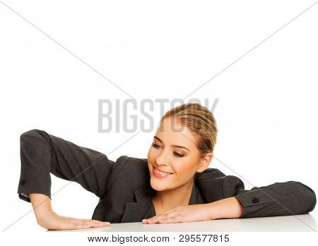 Businesswoman is lifting herself on desk with smile, isolated on white background.