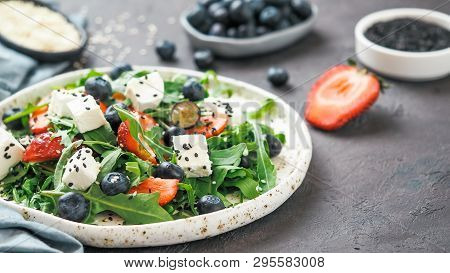 Salad With Arugula, Feta Cheese And Berries - Strawberry, Blueberry, In Craft Plate On Black Bacgrou