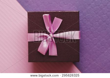 Small Gift Box With Pink Ribbon On Purple And Pink Background, Top View