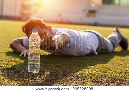 Thirsty Man On Grass At Sport Stadium Reach For A Bottle Of Pure Water.