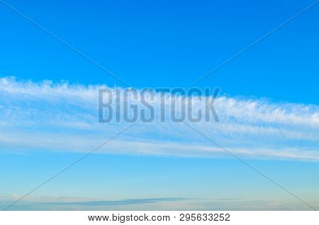 Blue sky background with white dramatic colorful clouds and sunlight, panoramic vast sky background. Sky landscape scene, blue sky background with white clouds in the sky lit by sunlight. Natural sky background, sky sunny landscape