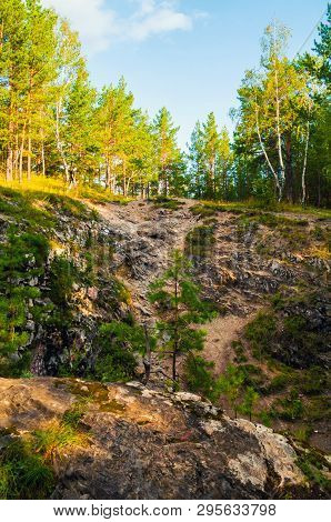 Summer forest mountain landscape - marble high steep near the Sugomak cave in Southern Urals, Russia. Forest mountain landscape, forest trees in the mountains. Forest mountain view