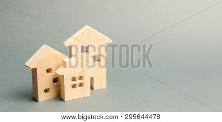 Miniature Wooden Houses On A Gray Background. Real Estate. Long-term Rental Apartments. Affordable H