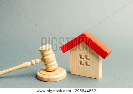 Miniature Wooden House And Judge's Hammer. The Concept Of Resolving Property Disputes. Property Alie