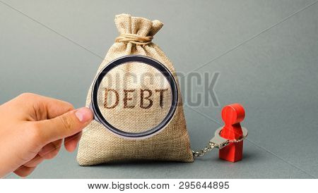 A Magnifying Glass Is Looking At A Money Bag With The Word Debt And A Borrower Is Bound By Handcuffs
