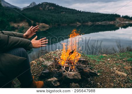 Hands Of Young Woman Warming Up By Camp Fire. Body Parts Of Adult Female At Nature. Camping. Fire.