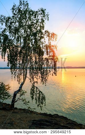 Summer sunset landscape - the Irtyash Lake in Southern Urals, Russia, rippled water surface lit by sunset summer light. Summer sunny water scene in soft tones