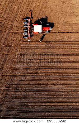 Aerial View Of Farmer And Tractor With Crop Seeder Mounted During Corn Planting In Field, Top View