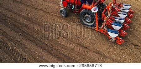 Aerial View Of Tractor With Mounted Seeder Performing Direct Seeding Of Crops On Plowed Agricultural