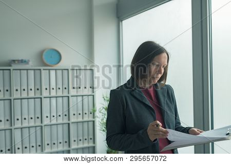 Concerned Businesswoman Reading Business Report Papers In Office, Financial Data Analysis And Strate