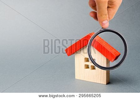 Wooden House And Magnifying Glass. Property Valuation. Home Appraisal. Choice Of Location For The Co