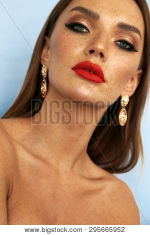 fashion photo of beautiful sexy woman with dark hair and cute freckles with bijou posing in studio poster