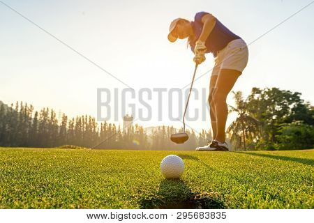 Sport Healthy. Golfer Asian Sporty Woman Focus Putting Golf Ball On The Green Golf On Sun Set Evenin