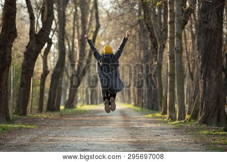 Excited Young Woman Is Jumping With Arms Raised Up In Spring Or Autumn.. Happiness, Success And Life