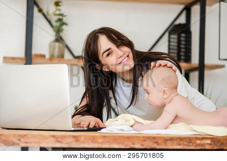 Young Mother With Baby Infant And Laptop