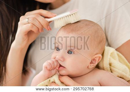 Female Hand Combing Hair Baby, Close Up.