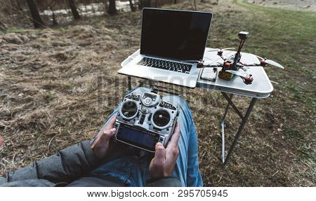 Fpv Drone Pilot. A Man Sits In A Chair With A Remote From The Fpv Drone In Front Of A Laptop And Con