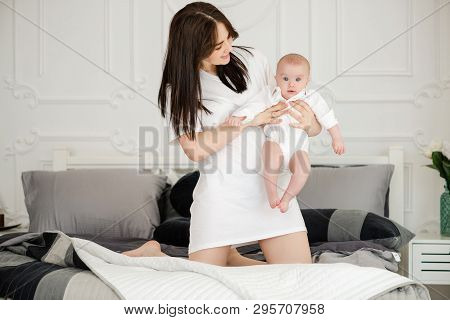 Mother And Baby Infant In White Outfit