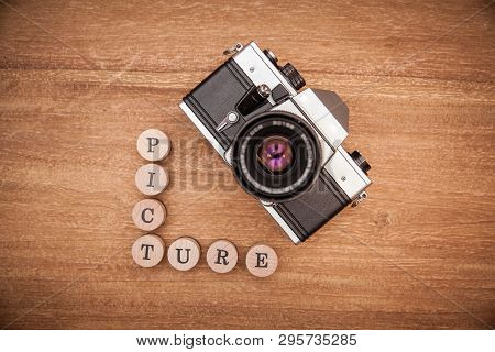 Old Photo Camera With Lens On Wooden Table. He Took A Picture Of A Lot Of Great And Memorable Moment