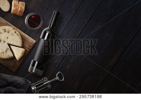 Red Wine Bottle, Corkscrew, Cheese, Wineglass, Bread On Black Wood Background, Top View, Copy Space.