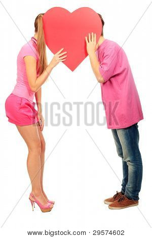 Happy young love couple kissing behind red heart. Isolated over white background.