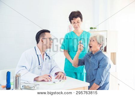 Asian Male Doctor Explain Method Of Asthma Inhaler To Senior Female Patient.