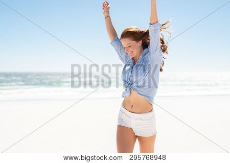 Happy mature casual woman enjoying tropical beach vacation. Smiling young woman having fun on her vacation at sea. Joyful lady with red hair enjoying freedom with outstreched arms, jumping on beach.