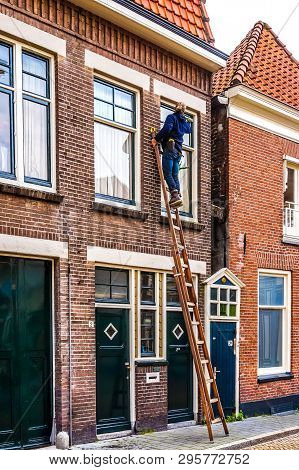 Zwolle, Overijsel/the Netherlands - Oct.23 2014: Traditional Window Washing Tradesman On An Extensio