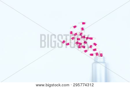 Pink-white Antibiotic Capsule Pills Spread Out Of White Plastic Drug Bottle. Antibiotic Drug Resista