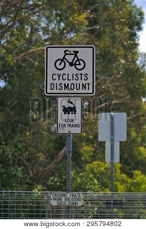 Cyclists Dismount And Look For Trains Sign