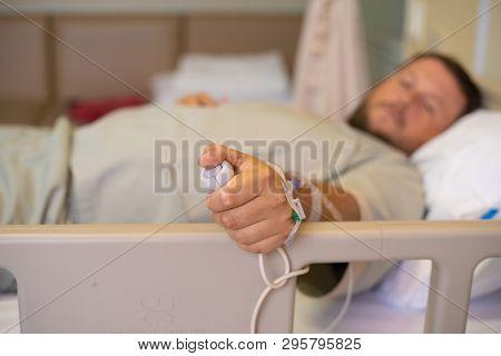 Man In A Hospital Room Calling A Nurse.a Hand Holding Emergency Button In Hospital Room.emergency Bu