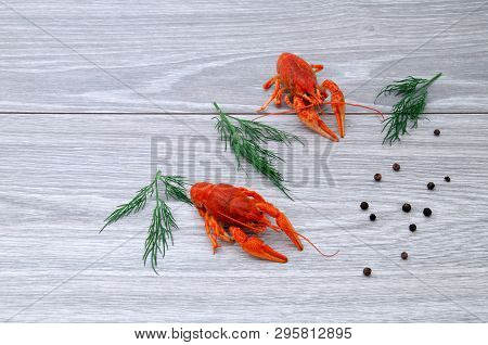 Boiled Crayfish With Peps On A Gray Wooden Background.