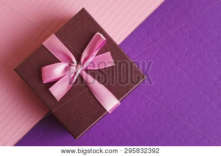 Decorative Gift Box With Pink Ribbon And Bow On Purple And Pink Background, Top View. Present For Bi