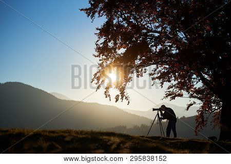 Tourist Photographer Using Tripod And Camera To Take Picture Of Mountain Panorama At Dusk And Settin