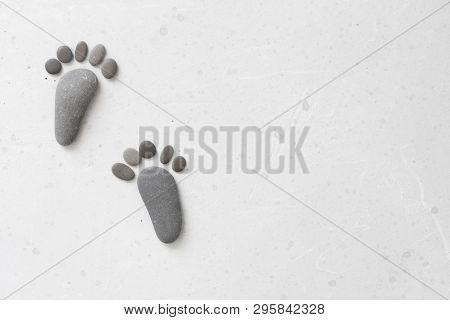 Footprints Made Of Stones. Happy Feet. Stone Arranged Like Footprints On The Beach. Spa Background W