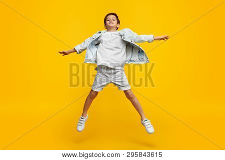 Funny Youngster In Trendy Outfit Stretching Out Arms And Jumping Against Yellow Background