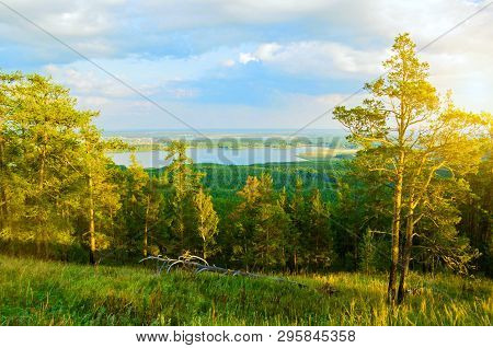 Forest spring landscape with forest spring trees, mountain slopes and lake under soft sunset light, natural spring forest mountain landscape