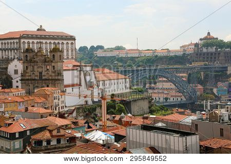 Porto, Portugal. Cityscape Of Old Town With Tiled Roofs, Ponte Dom Luis I Bridge, Saint Lawrence Chu