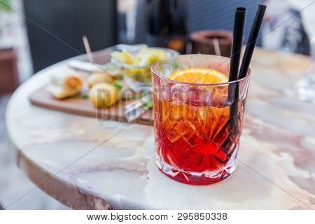 Mezcal Negroni Cocktail Italian Aperitivo On The Table In The Open Area Of Restaurante