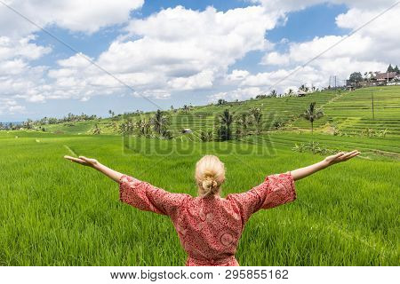 Relaxed Fashionable Caucasian Woman Wearing Red Asian Style Kimono, Arms Rised To Sky, Enjoying Pure