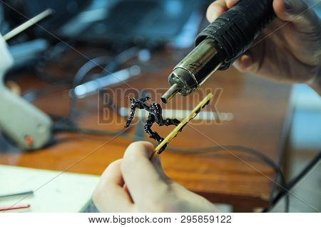 figurine making sculptor hands. man sculpting handmade toy bee from plastic glue, house decoration craftsmanship hobby, decor creation process poster