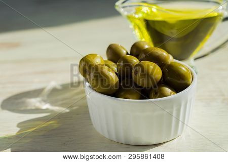 Glass Sauceboat With Extra Virgin Olive Oil And Fresh Green Olives On Wooden Table.