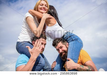 Men Carry Girlfriends On Shoulders. Summer Vacation And Fun. Couples On Double Date. Inviting Anothe
