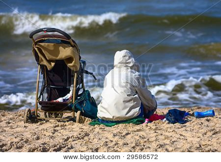 Mother and baby carriage on the beach