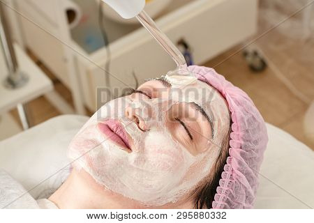 poster of Young woman in beauty salon does rejuvenating, toning procedure darsonval on the face.