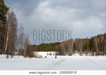 Fishermen On The Ice Of A Small River On A Cloudy Spring Day.