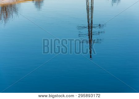 A Beautiful Reflection Of The Power Line In The Mirror Smooth Surface Of The River.