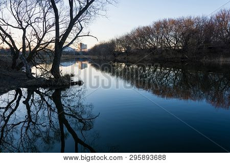 Beautiful Cityscape With A Small River And Bare Branches Of Trees In The Evening.