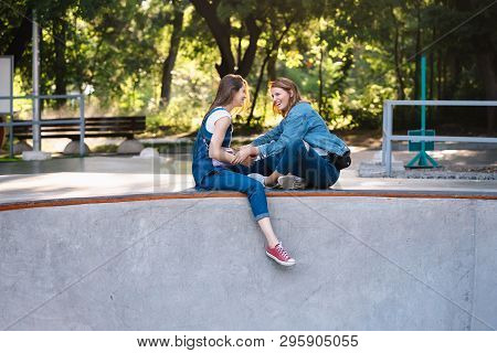 Two Happy Young Girls Sitting At The Skate Park