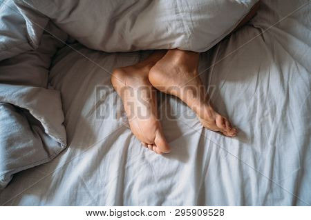Close-up Woman Feet Alone In White Bed